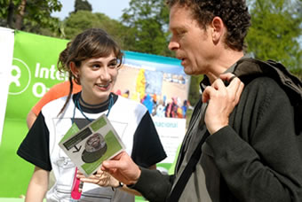Voluntaria brindando información a un hombre en el Día de la esperanza en Barcelona. (c) Pablo Tosco / Oxfam Intermón