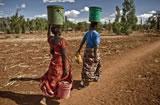 Dos mujeres transportando agua en cubos en la comunidad de Manchali. (c) Pablo Tosco / Oxfam Intermón