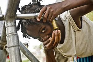 Una niña bebe agua en un punto de distribución del campo de desplazados de la Universite de Quisqueya en Puerto Príncipe. (c) Pablo Tosco / Oxfam Intermón