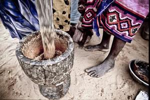 Un grupo de mujeres moliendo cereales en un mortero en el campo de refugiados sudaneses de Djabal. (c) Pablo Tosco / Oxfam Intermón