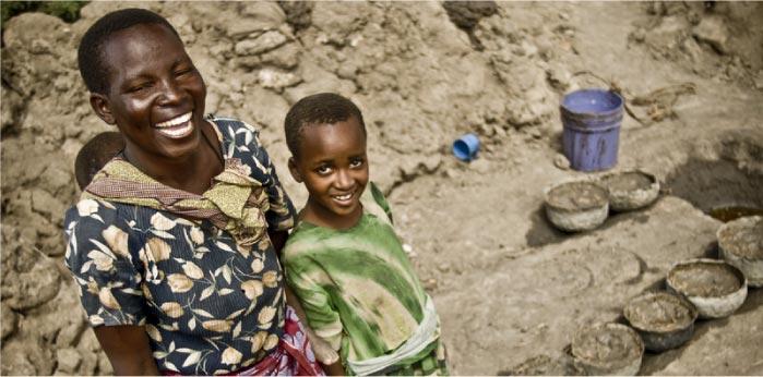 Una mare amb els seus fills a un pou a Uganda. (c) Pablo Tosco / Oxfam Intermón